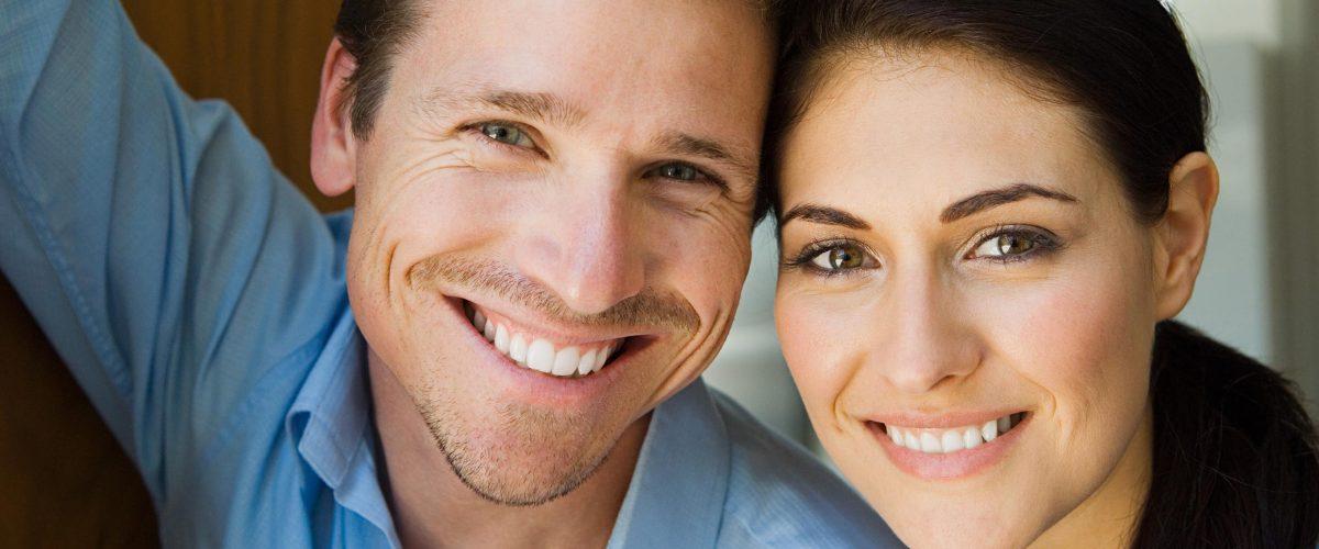 Lächelndes Paar. Keramikimplantate: natürlicher und ästhetischer Zahnersatz aus Zirkonoxid.